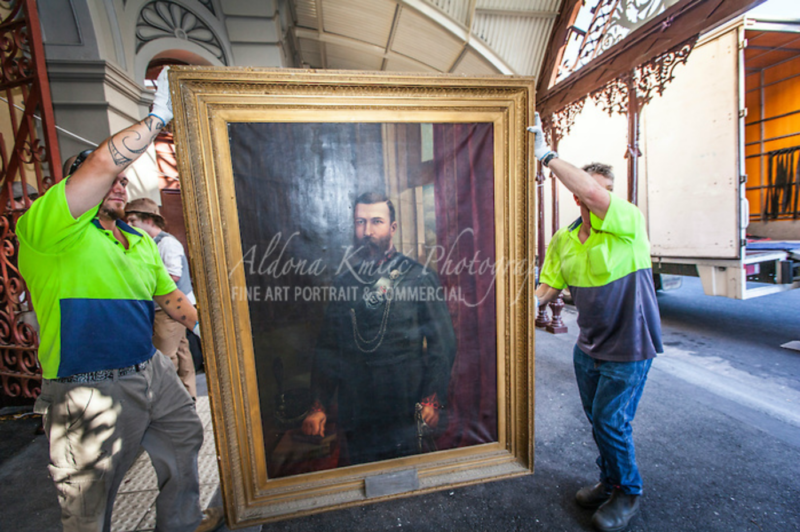 Two men carrying a framed portrait painting from The Mining Exchange on Lydiard Street (Aldona Kmiec/© Aldona Kmiec 2013 www.aldonakmiec.com)